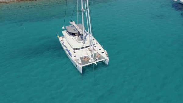 Aerial View of a Anchored Catamaran Yacht Standing with People Sunbathing on it's Deck. Boat Stands in Azure Sea Waters With Coral Reef Visible. Royalty-free stock video