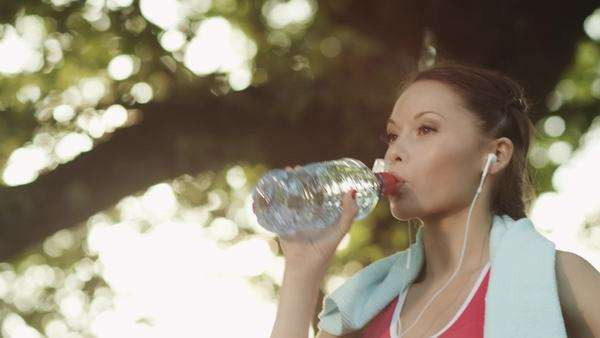 Girl drinking water during sport training in park, jib shot Royalty-free stock video