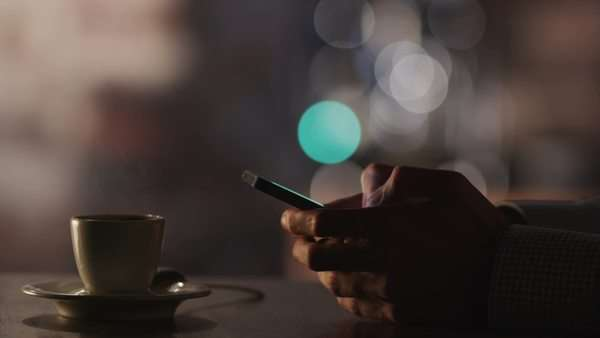 Man typing a message using mobile phone at evening time in coffee house. Royalty-free stock video