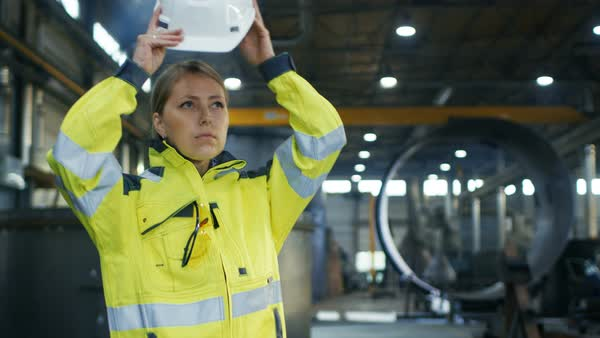 Female industrial worker puts on protective hard hat while walking through heavy industry manufacturing factory Royalty-free stock video