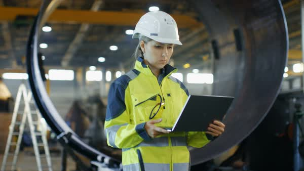 Female industrial engineer in the hard hat and safety jacket uses laptop computer while standing in the heavy industry manufacturing factory Royalty-free stock video