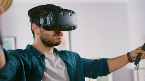 4815dd98e00f Energetic young man wearing virtual reality headset and holding controllers  plays in a video game at