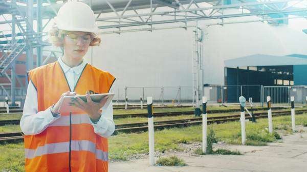 Woman in hard hat and safety vest is using tablet pc on railway station Royalty-free stock video