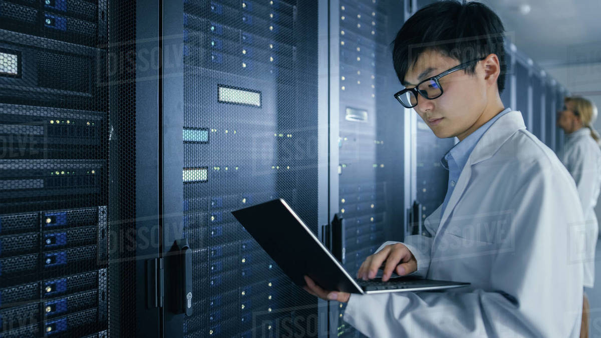 In Data Center: Male and Female IT Specialists Wearing White Coats Work with Server Racks, Use Laptops to Run Maintenance Diagnostics. People wearing Lab Coats Working with Datacenter Database. - Stock Photo -