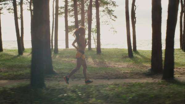 Young girl is running in forest at morning time Royalty-free stock video