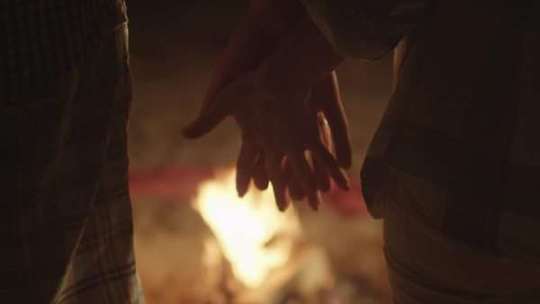 Couple is holding hands near campfire at night Royalty-free stock video