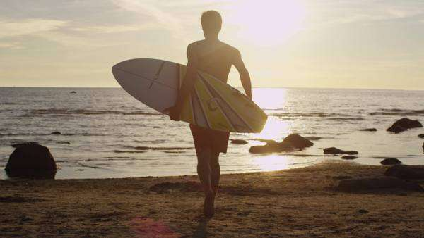 Young man with surfboard is running into water in sunset light Royalty-free stock video