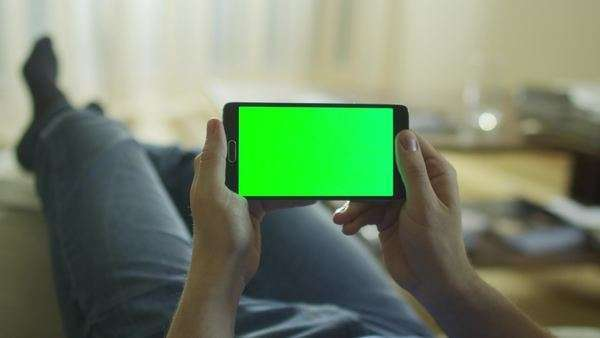 Man is laying on couch at home and holding android phone with green screen in landscape mode. Royalty-free stock video
