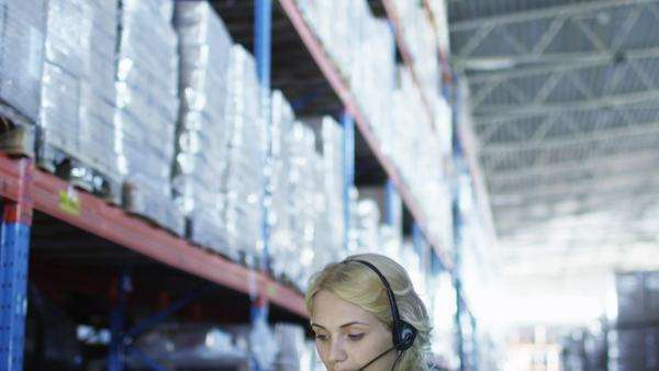 Female worker of logistic warehouse is working on laptop. Wears headset. Royalty-free stock video
