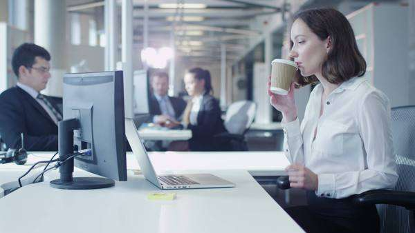 Female office worker is working on laptop and drinking coffee Royalty-free stock video