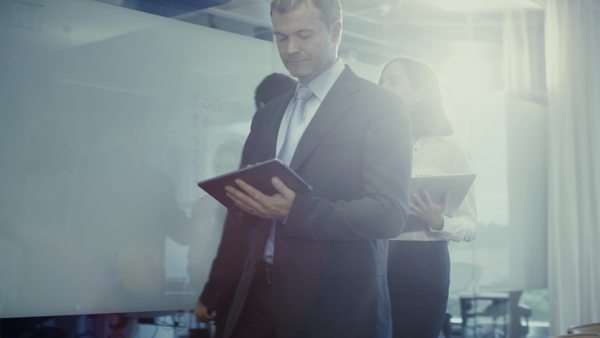 Businessman and his secretary are walking through office. He is  holding tablet in hands. Royalty-free stock video