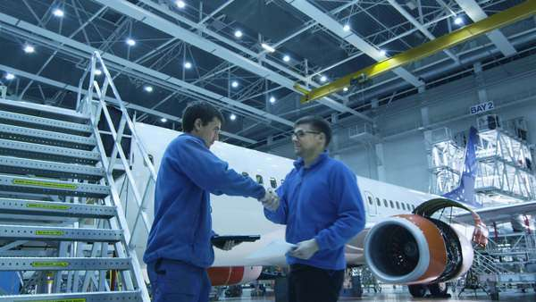 Aircraft maintenance mechanic is going down the stairs while using tablet and greeting his colleague a the bottom in a hangar. Royalty-free stock video