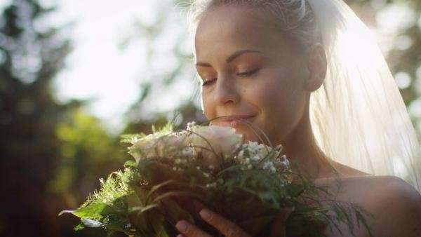 Portrait of a bride in wedding dress with flowers in a sunny park. Royalty-free stock video
