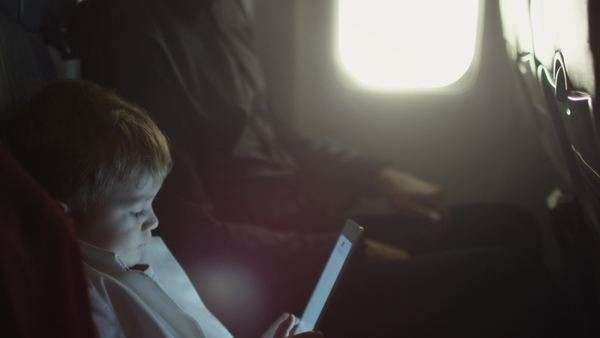 Young boy is playing with tablet on an airplane while father talks to him next to a window. Royalty-free stock video