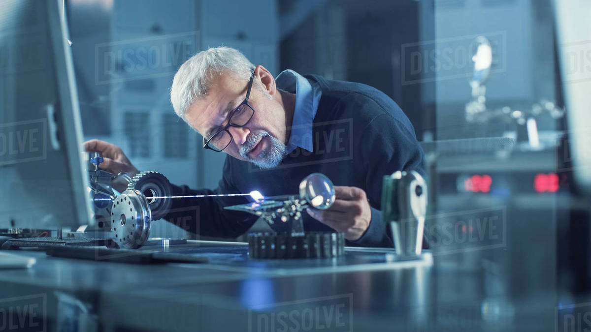 Portrait of Focused Middle Aged Engineer in Glasses Working with High Precision Laser Equipment, Using Lenses and Testing Optics for Accuracy Required Electronics Royalty-free stock photo