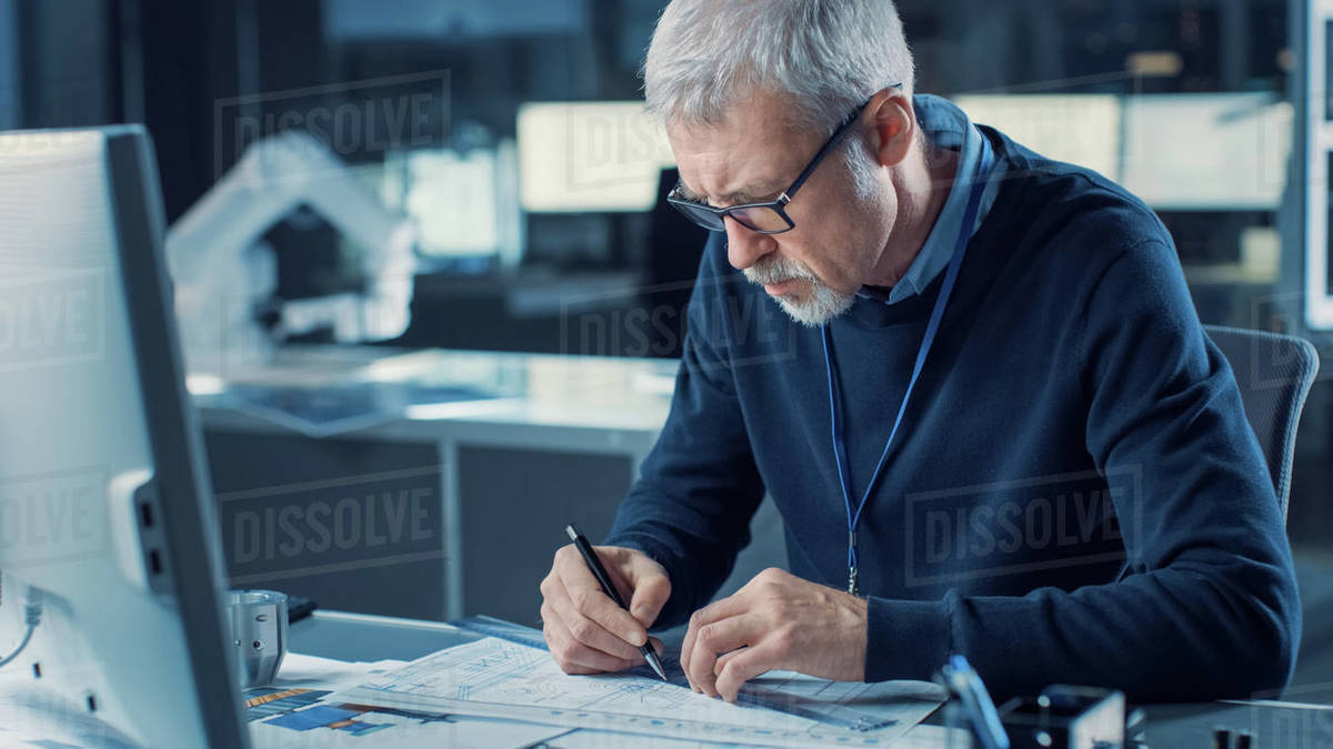 Professional Heavy Industry Engineer Draws Engine Concept Blueprint, References Computer. Engineering Bureau and Industrial Design Agency with Various Robotic, Architectural and Machinery Components Royalty-free stock photo
