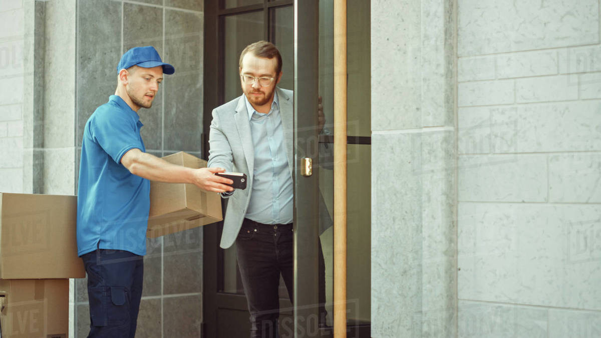 Delivery Man Takes Postal Package from a Customer who Signs Electronic Signature POD Device. Loads Delivery into His Truck / Van. In Business District Courier Takes Cardboard Box Parcel from a Man Royalty-free stock photo