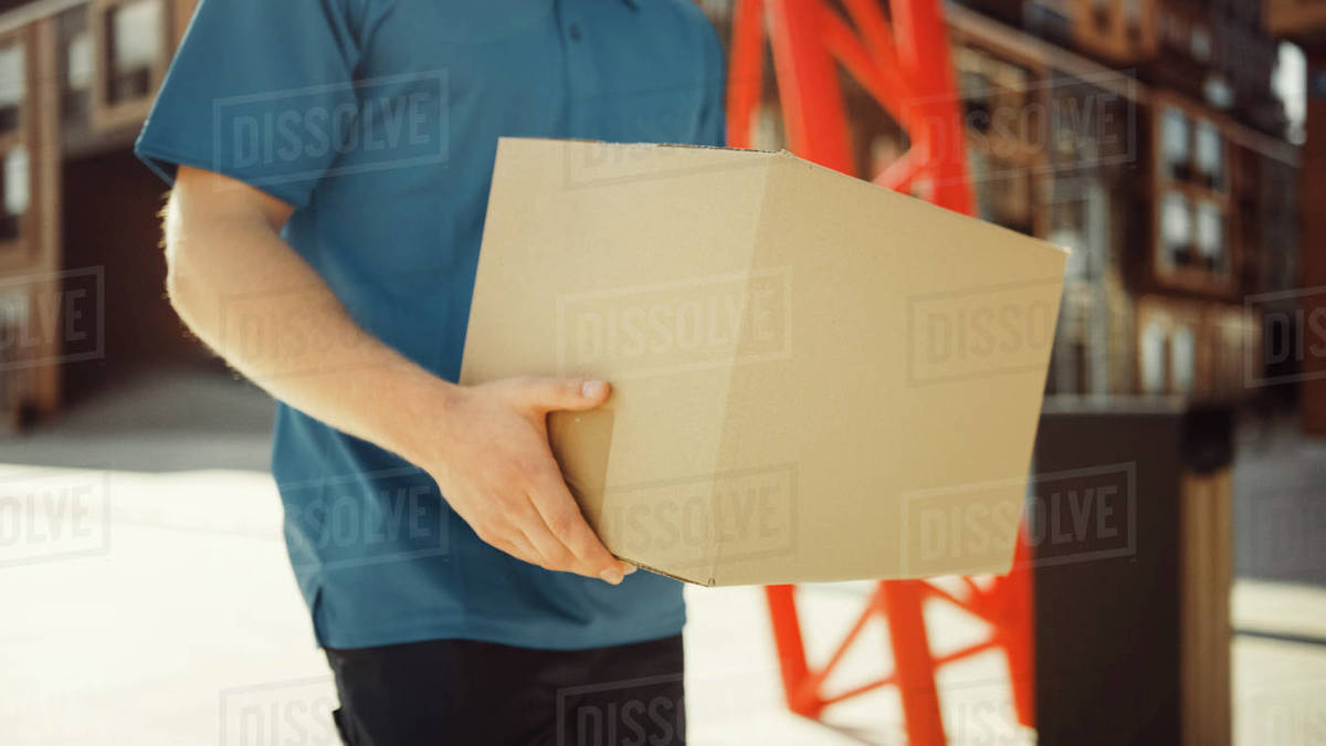 Delivery Man Holds Cardboard Box Package Walks Through Modern Stylish Business District. Courier On the Way to Deliver Postal Parcel to a Client. Focus on the Package. Royalty-free stock photo