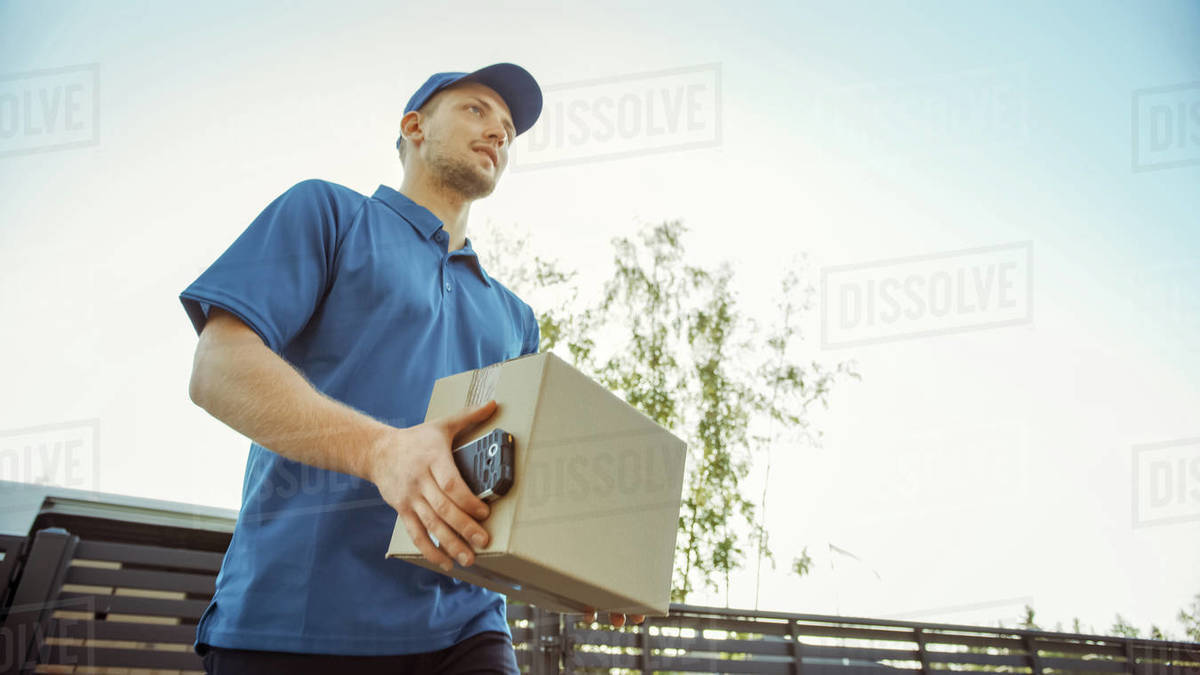 Low Angle Shot of Beautiful Young Delivery Man Delivering Cardboard Box Package. Courier Delivering Parcel in the Suburban Neighborhood. Royalty-free stock photo