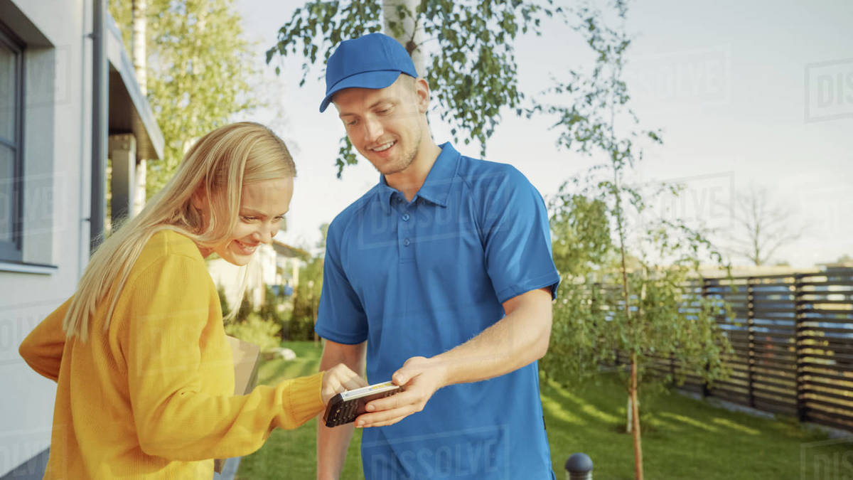 Beautiful Young Woman Meets Delivery Man who Gives Her Cardboard Box Package, She Signs Electronic Signature POD Device. Courier Delivering Parcel in the Suburban Neighborhood. Royalty-free stock photo