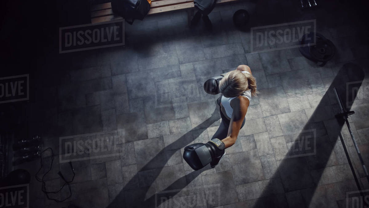 Professional Female Boxer Exercises Air Punches while Wearing Sportswear and Fighting Gloves in the Hardcore Gym. Strong Beautiful Girl Kickboxing and Self Defense Workout. Top Dramatic View Royalty-free stock photo