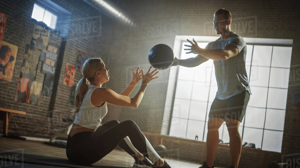 Beautiful Young Girl Exercises with Personal Trainer, Doing Sit-ups with Medicine Ball, Throwing Pass Back and Forth. Fit and Strong Couple Workout. Exercising Strength, Cardio and Power. Royalty-free stock photo