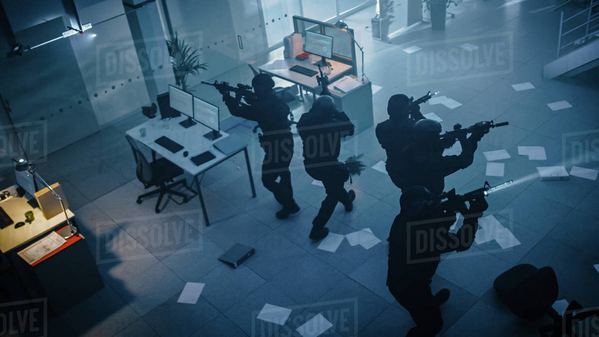 Masked Squad of Armed SWAT Police Officers Storm a Dark Seized Office Building with Desks and Computers. Soldiers with Rifles and Flashlights Move Forwards and Cover Surroundings. Above-view Camera. Royalty-free stock photo