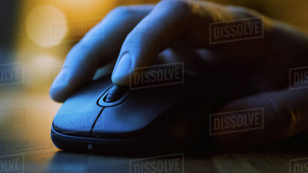 Close-up Macro Shot: Person's Hand Using Wireless Computer Mouse, Scrolls through Apps and Websites with a Wheel and Clicks on Buttons. In the Background Evening Light Royalty-free stock photo