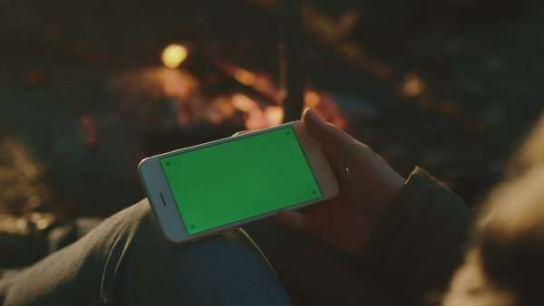 Girl is holding a smartphone in landscape mode with green screen mock-up next to a campfire in the evening. Royalty-free stock video