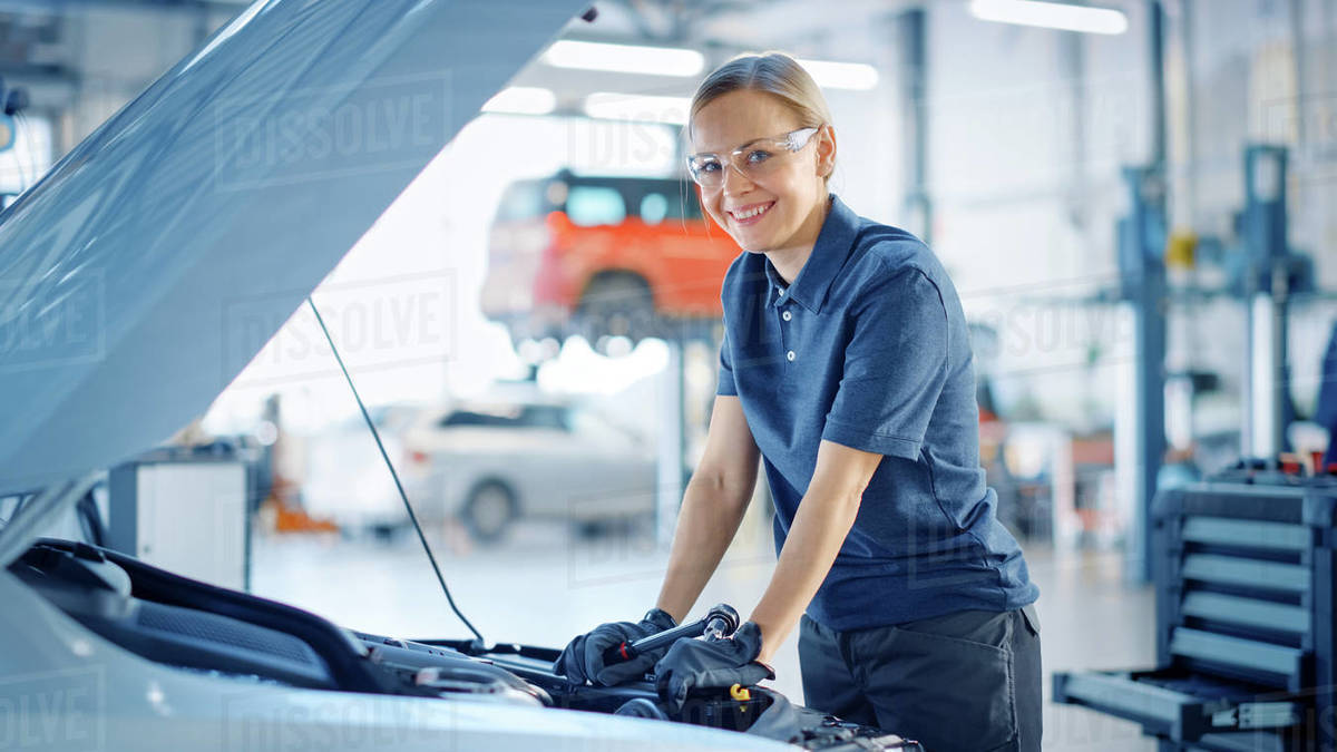 Beautiful Empowering Female Car Mechanic is Posing in a Car Service. She Wears Safety Glasses. Specialist Looks at a Camera and Smiles. Royalty-free stock photo