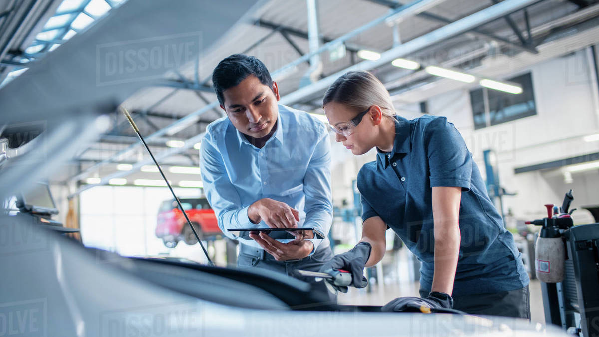 Instructor with a Tablet Computer is Giving a Task for a Future Mechanic. Female Student Inspects the Car Engine. Assistant is Checking the Cause of a Breakdown in the Vehicle in a Car Service. Royalty-free stock photo
