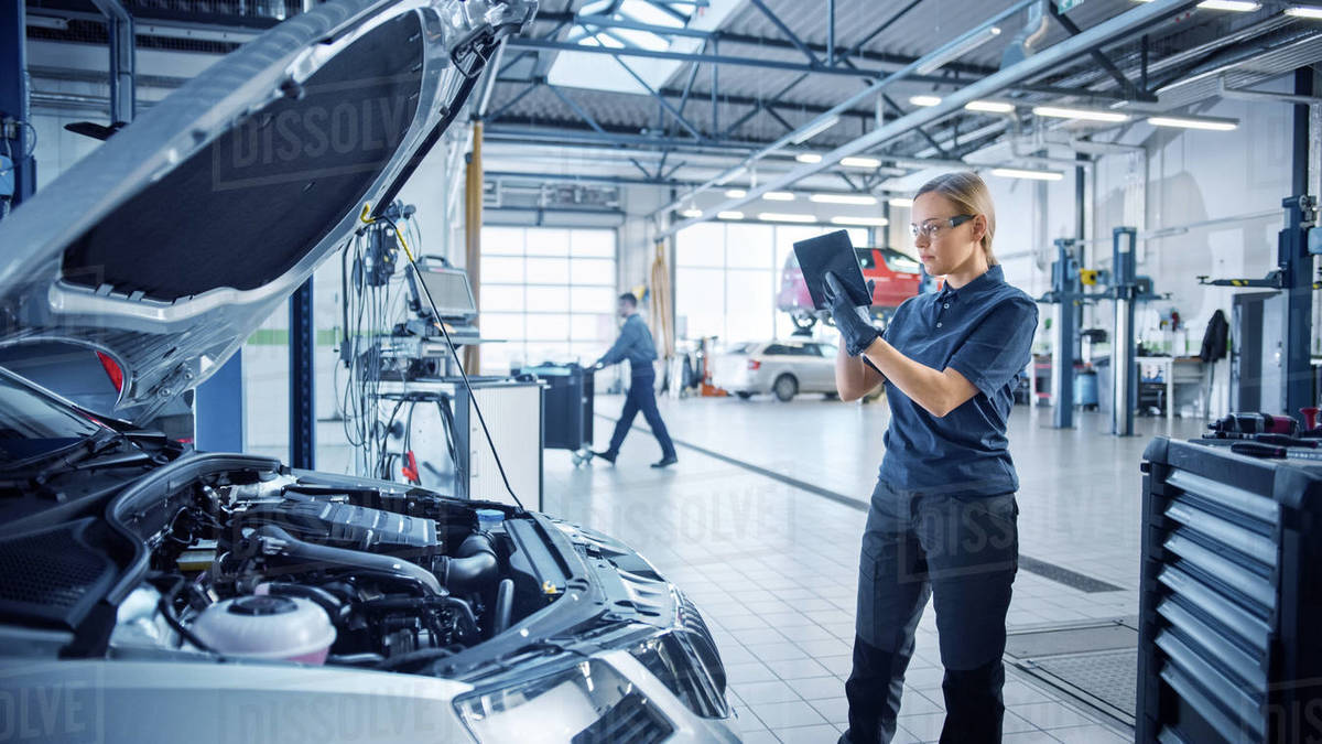 Female Mechanic Uses a Tablet Computer with an Augmented Reality Diagnostics Software. Specialist Inspecting the Car in Order to Find Broken Components Inside the Engine Bay. Modern Car Service. Royalty-free stock photo