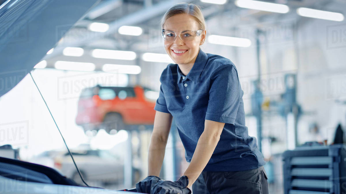 Beautiful Empowering Female Car Mechanic is Working on a Vehicle in a Service. She Looks Happy While Using a Ratchet. Specialist is Wearing Safety Glasses. She Looks at a Camera and Smiles. Royalty-free stock photo