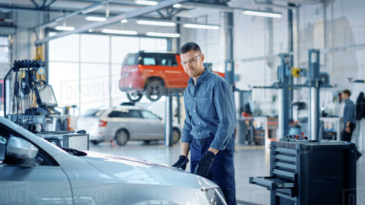 Handsome Professional Car Mechanic is Working on a Vehicle in a Service. Happy Repairman is Closing the Hood. Specialist is Wearing Safety Glasses. He Looks at a Camera and Smiles. Royalty-free stock photo