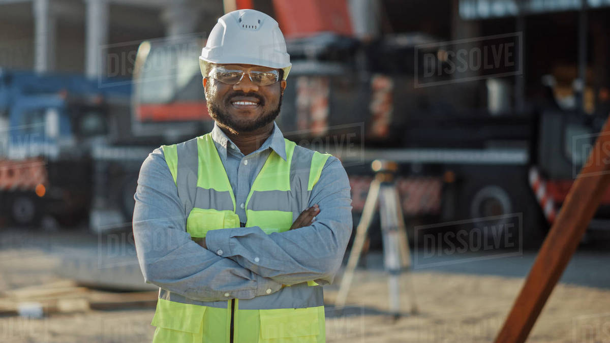 Portrait of Successful Contractor / Investor / Architectural Engineer Wearing Hard Hat and Safety Vest Standing on a Commercial Building Construction Site, Crosses Arms Confidently. In the Background Crane Machinery Royalty-free stock photo