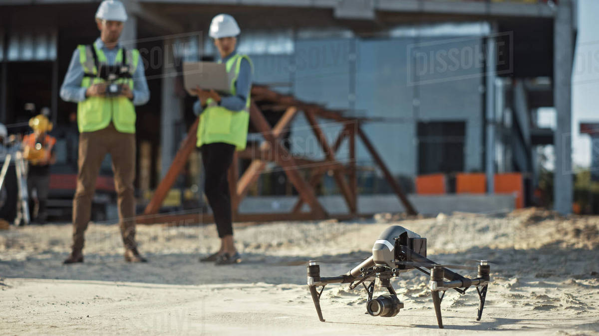 Two Specialists Use Drone on Construction Site. Architectural Engineer and Safety Engineering Inspector Fly Drone on Commercial Building Construction Site Controlling Design and Quality. Focus on Drone Royalty-free stock photo