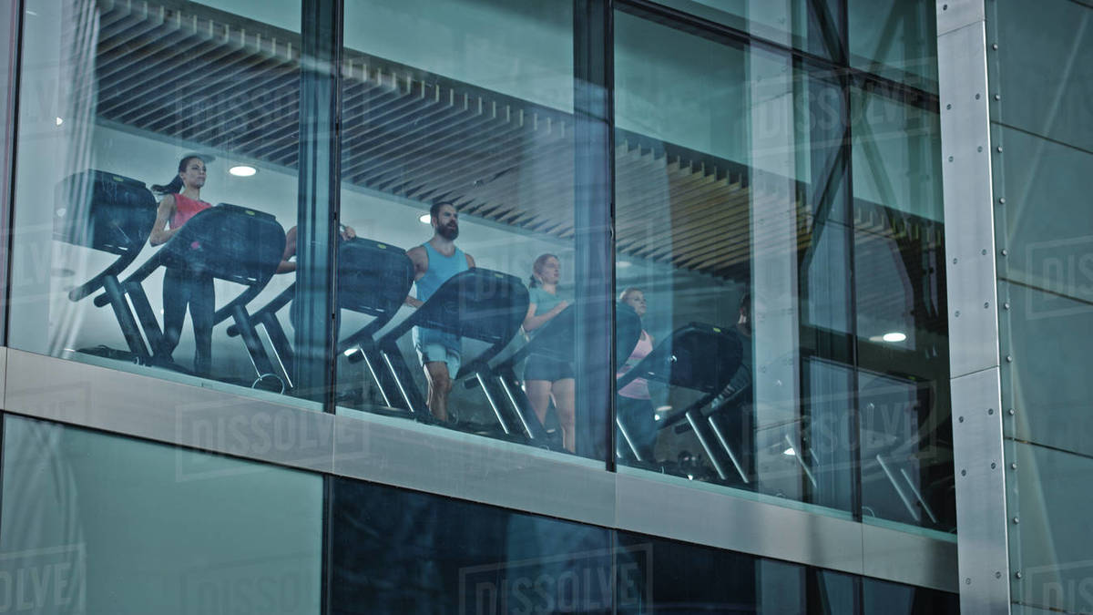 Athletic People Running on Treadmills, Doing Fitness Exercise. Fit and Muscular Athletes Actively Training in the Modern Gym. Sports People Workout. Low Angle Shot From Outside the Building Royalty-free stock photo