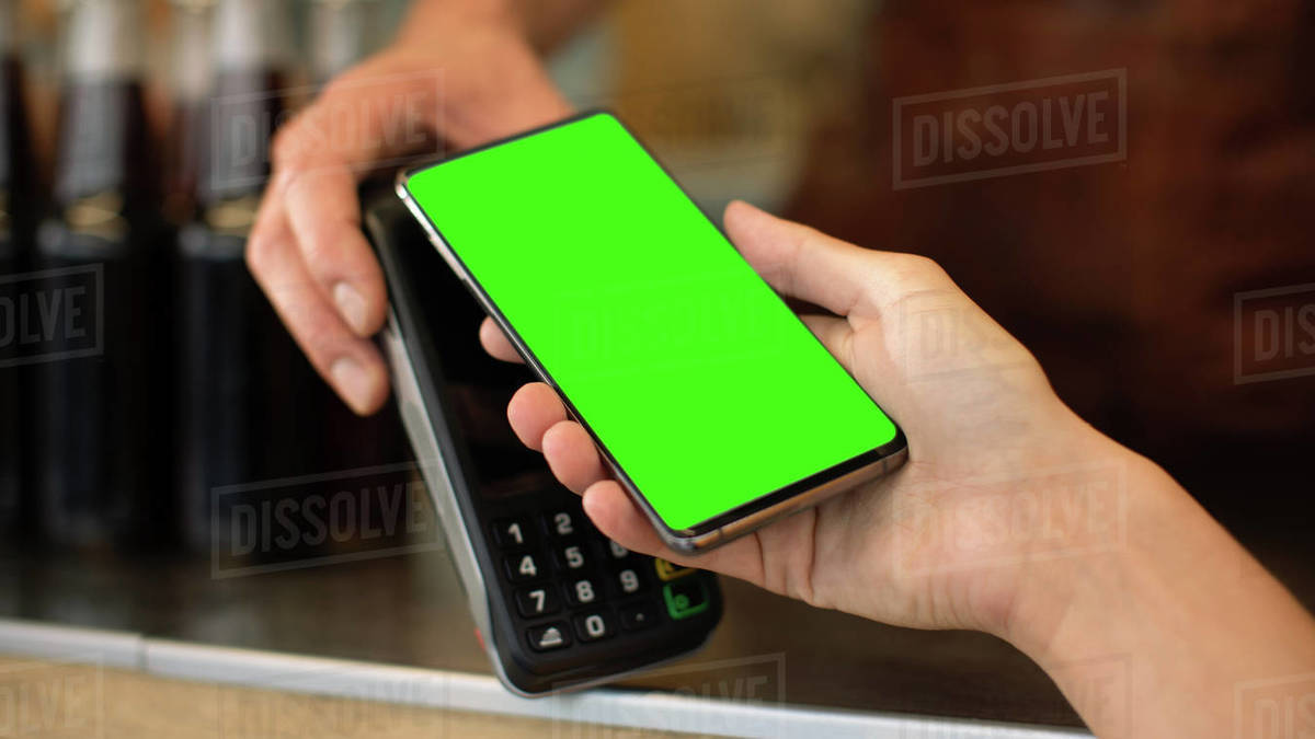 Young Woman is Using Her Smartphone with Green Screen for Contactless Payment. She is Paying for Gourme Street Food. Eco Friendly Gluten Free Food Court Selling Modern Fusion Cuisine Royalty-free stock photo