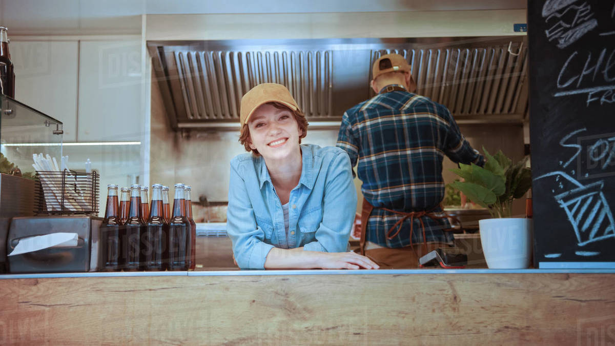 Food Truck Female Employee Smiles and Looks at the Camera. Street Food Truck Selling Burgers in a Modern Neighbourhood. Successful Street Food Business Owner is Happy at Work. Brunette Wears a Cap. Royalty-free stock photo