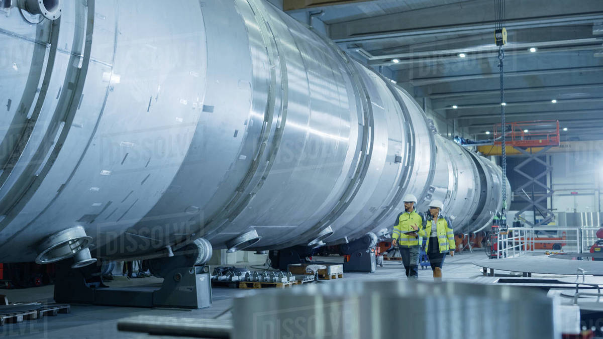 Two Heavy Industry Engineers Walking Through Pipe Manufacturing Facility, Use Digital Tablet, Have Discussion. Modern Industrial Design and Construction of Oil, Gas and Fuels Transport Pipeline Royalty-free stock photo