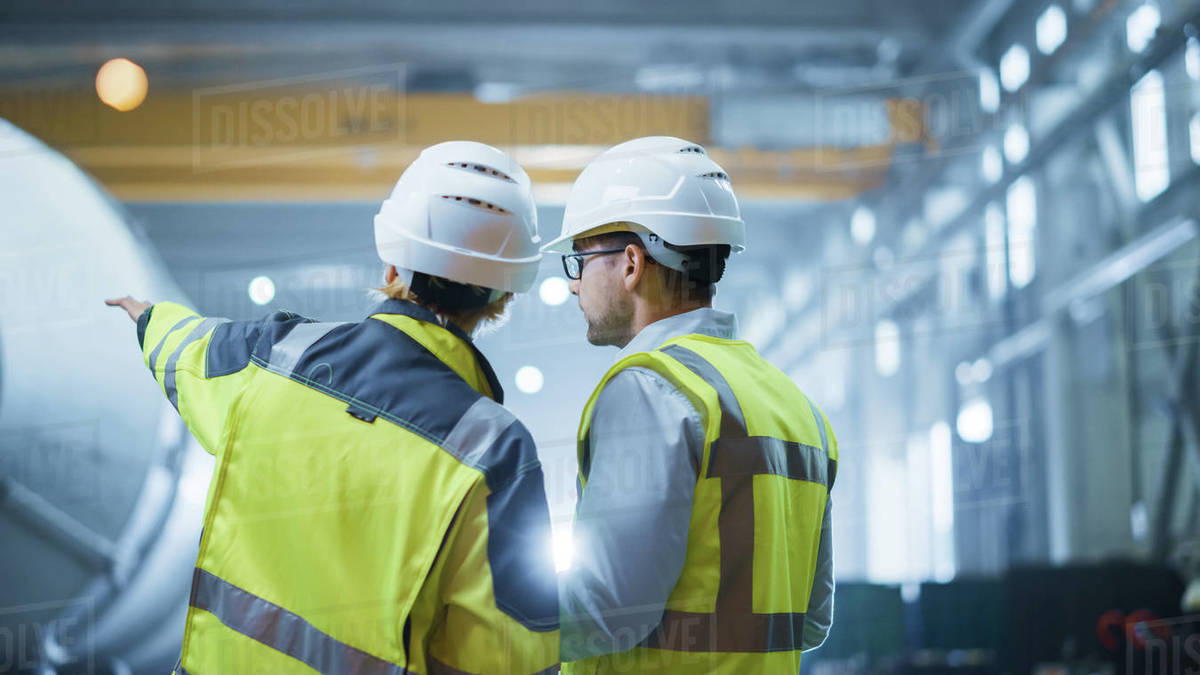 Two Heavy Industry Engineers Stand in Pipe Manufacturing Factory, Use Digital Tablet Computer, Have Discussion. Construction of Oil, Gas and Fuels Transport Pipeline. Back View Sparks Flying Royalty-free stock photo