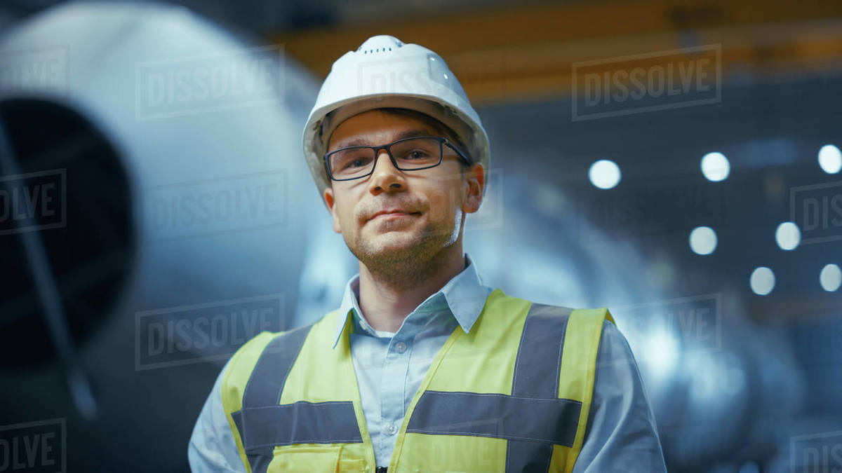Portrait of Young Professional Heavy Industry Engineer / Worker Wearing Safety Vest and Hardhat Smiling on Camera. In the Background Unfocused Large Industrial Factory where Welding Sparks Flying. Royalty-free stock photo