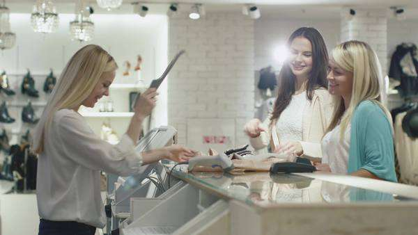 Two cheerful girls are checking out at a cash desk in a department store. Royalty-free stock video