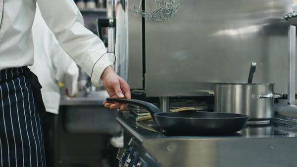 Professional chef in a commercial kitchen is preparing food on a pan. Royalty-free stock video