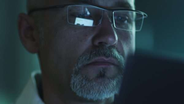 Portrait of middle-aged male using tablet and have reflections of screen in glasses Royalty-free stock video