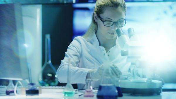 Woman scientist in glasses does chemical research and using microscope Royalty-free stock video