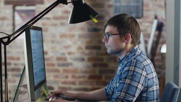 Young designer in glasses is sitting in front of a monitor in a loft and sketching on a graphic tablet. Royalty-free stock video