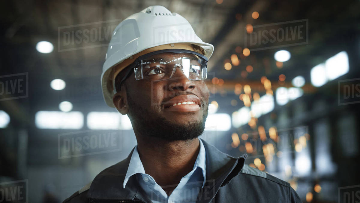 Happy Professional Heavy Industry Engineer/Worker Wearing Uniform, Glasses and Hard Hat in a Steel Factory. Smiling African American Industrial Specialist Standing in a Metal Construction Manufacture. Royalty-free stock photo