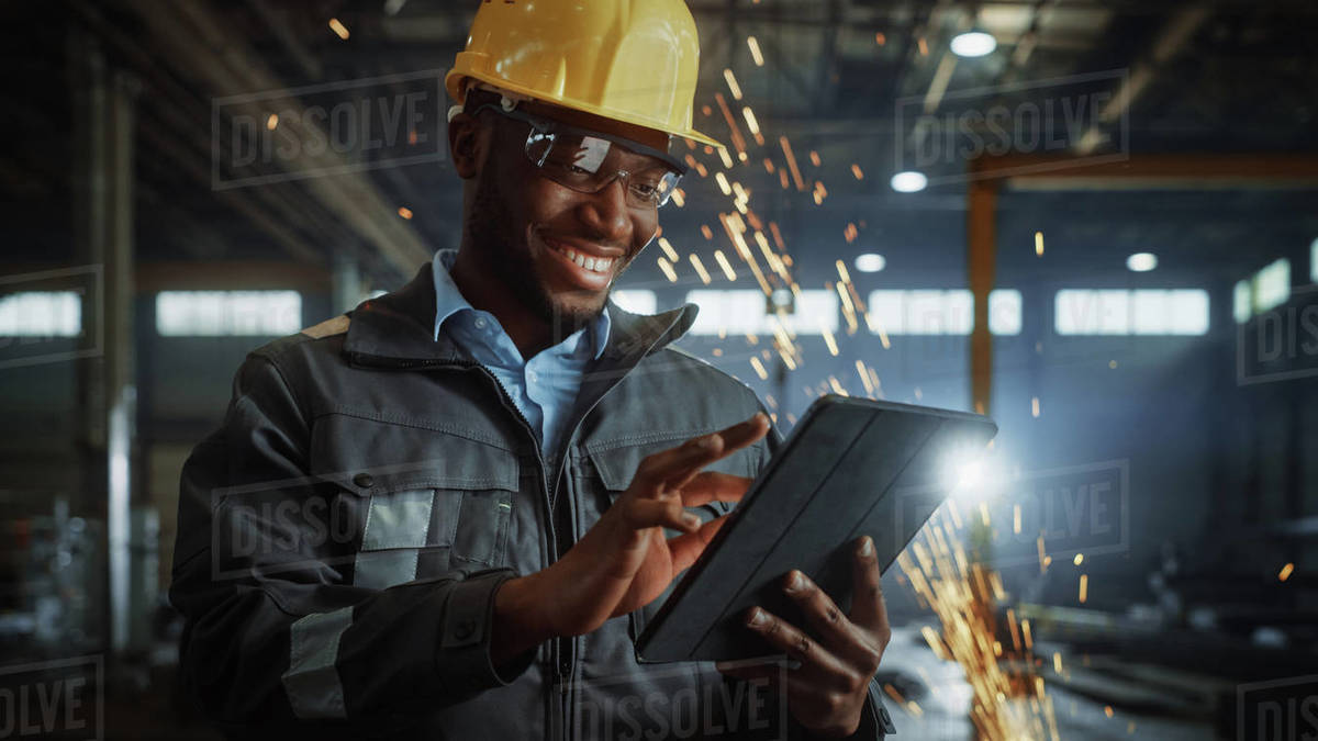 Professional Heavy Industry Engineer/Worker Wearing Safety Uniform and Hard Hat Uses Tablet Computer. Smiling African American Industrial Specialist Standing in a Metal Construction Manufacture. Royalty-free stock photo