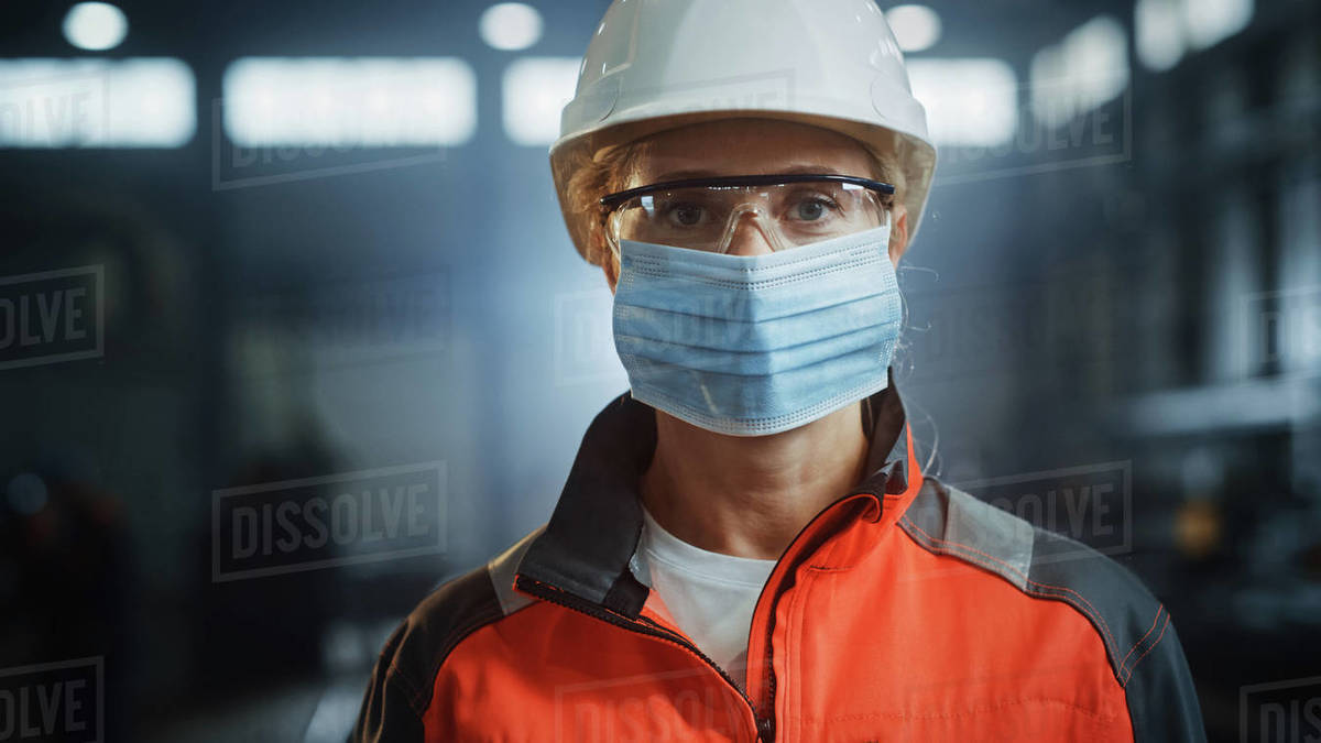 Portrait of a Professional Heavy Industry Engineer Worker Wearing on Safety Face Mask in a Steel Factory. Beautiful Female Industrial Specialist in Hard Hat Standing in Metal Construction Facility. Royalty-free stock photo